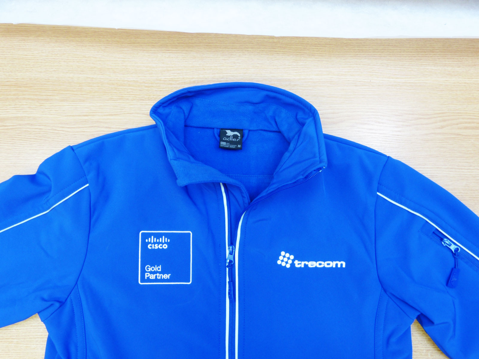 Wykonanie kurtki typu softshell z logo na prawej i lewej stronie.