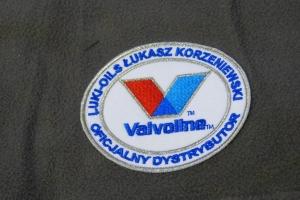 Naszywka z logo firmy przyszyta na bluze polarową.