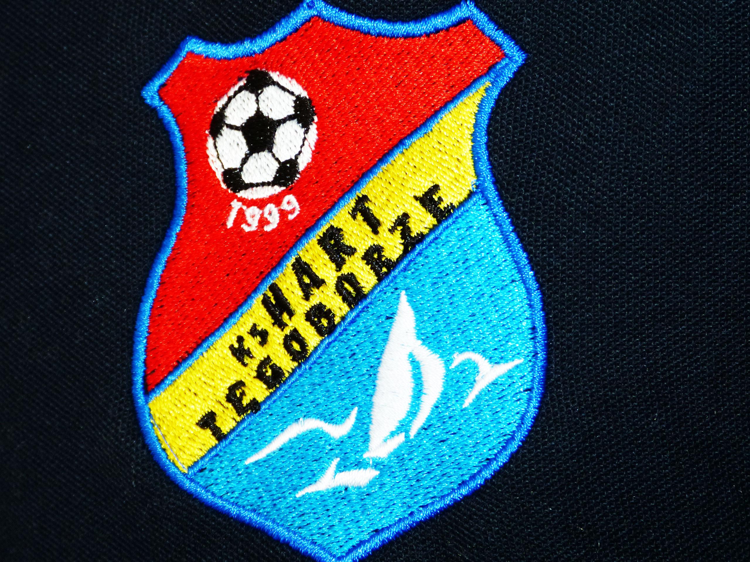 Haftowany herb piłkarski na koszulce polo.